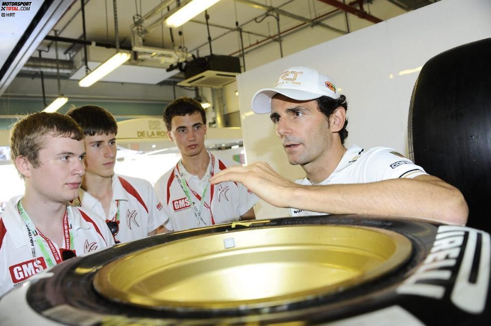 Pedro de la Rosa (HRT) und Narain Karthikeyan (HRT) mit einem Formel-1-in-der-Schule-Team