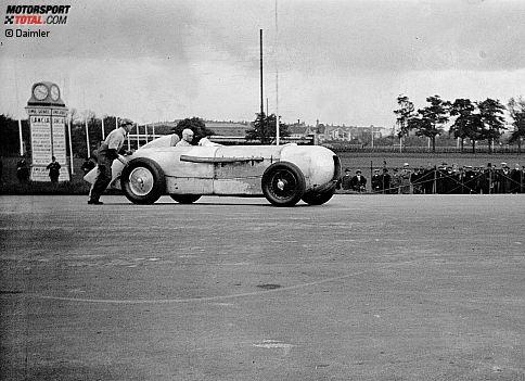 """Die Geburtsstunde eines Mythos: Manfred von Brauchitsch gewinnt mit seinem Mercedes-Benz SSKL das Avus-Rennen 1932 in der Klasse über 1,5 Liter Hubraum. Weil die Verkleidungsbleche unlackiert sind, entsteht die auffällige Aluminium-Optik. Der Streckensprecher erwähnt erstmals den Begriff """"silberner Pfeil""""."""