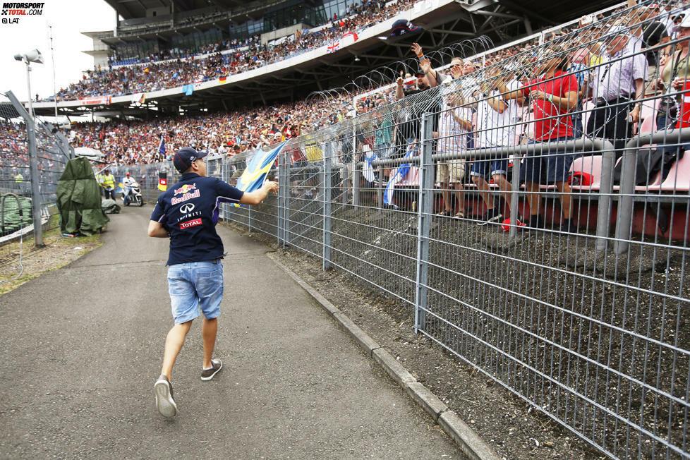 Die, die da sind, sorgen aber für gute Stimmung. Zum Beispiel während der Fahrerparade, als Sebastian Vettel im Motodrom aus seinem Oldtimer springt und signierte Red-Bull-Kappen verteilt.