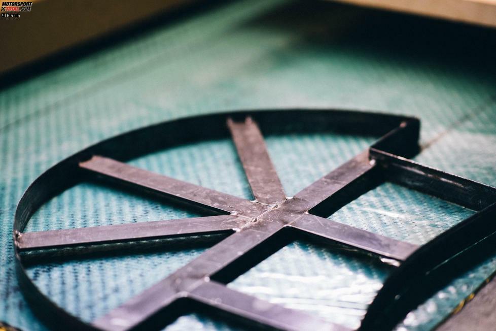 Die vorimprägnierten Teile aus Kohlefaser-Verbundstoff werden in spezifische Formen geschnitten, bevor sie in eine muschelförmige Schablone kommen.