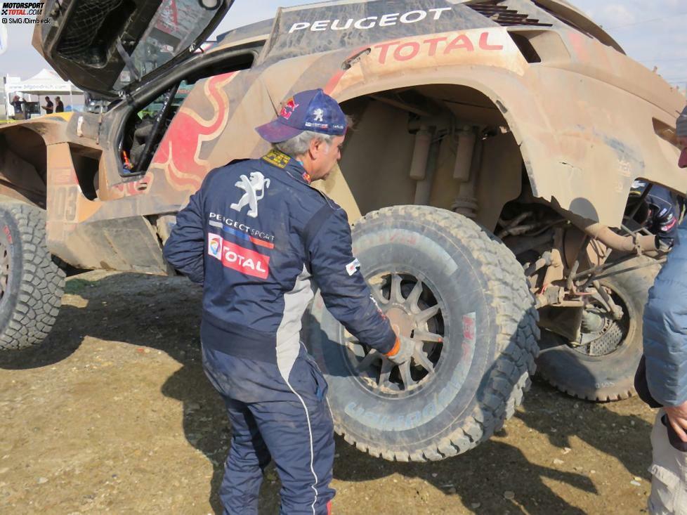 Bei einer Marathon-Etappe sind die Fahrer auf sich alleine gestellt und müssen Wartungen und Reparaturen selbstständig durchführen. Carlos Sainz beginnt schon mal mit dem Reifenwechsel.