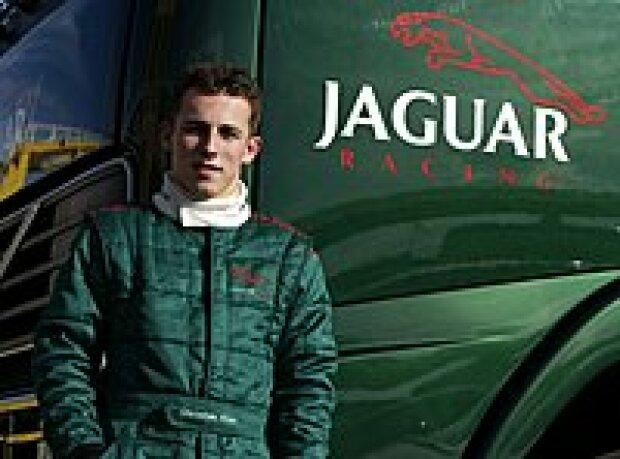 Christian Klien vor einem Renntransporter des Jaguar-Teams