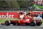 Fernando Alonso (Ferrari) jubelt, während im Bildhintergrund das Auto von Sebastian Vettel (Red Bull) geborgen wird.