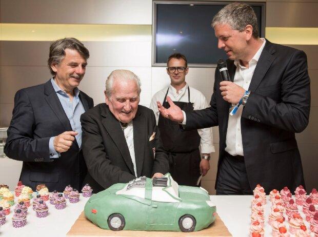 44. AvD Oldtimer Grand-Prix: Renn- und Testfahrerlegende Norman Dewis schneidet seine Geburtstagstorte zum 96. an. Links Jaguar Land Rover-Chef Dr. Rolf Speth, rechts Deutschland-Chef Peter Modelhart.