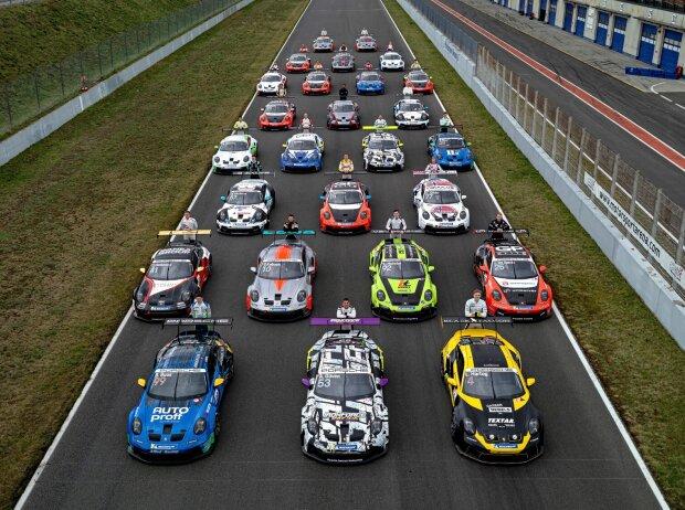 Schräg von oben fotografiert alle Autos des Porsche Carrera Cup Deutschland neben- und hintereinander auf einer Gerade aufgereiht.