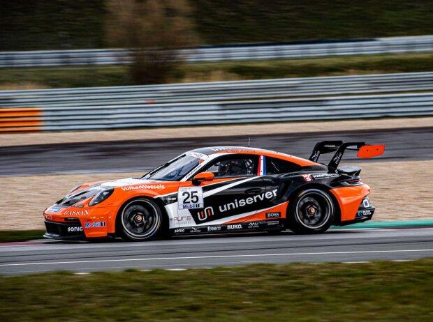 Seitenansicht eines orange-schwarzes Auto des Porsche Carrera Cup Deutschland auf der Strecke