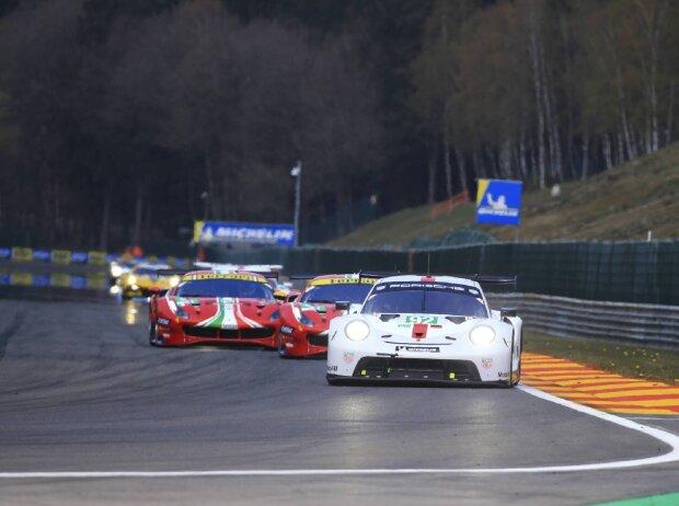 Ein weißer Porsche fährt vor zwei roten Ferraris auf der Rennstrecke in Spa