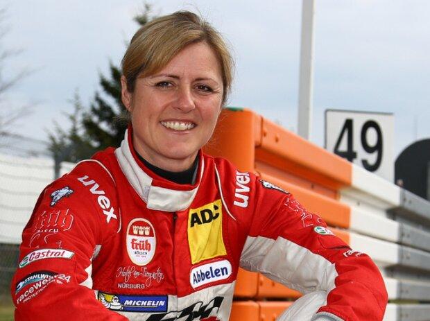 Sabine Schmitz posiert auf einem Randstein der Nürburgring-Nordschleife