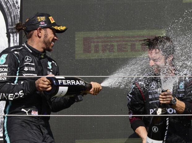 Formel 1 2021: Lewis Hamilton feiert seinen Sieg beim Grand Prix von Großbritannien 2021 in Silverstone mit Champagner der Marke Ferrari und einem Mercedes-Mitarbeiter