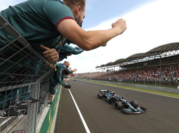 Mitglieder von Aston Martin bejubeln die Zieldurchfahrt von Sebastian Vettel im Aston Martin AMR21 auf Platz zwei beim Grand Prix von Ungarn der Formel 1 2021 auf dem Hungaroring bei Budapest
