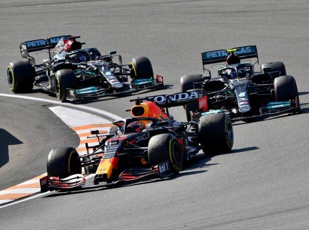Max Verstappen en un Red Bull RB16B frente a un Mercedes W12 de Valtteri Bottas y Lewis Hamilton en el Gran Premio de Fórmula 1 de Holanda 2021 en Zandvoort