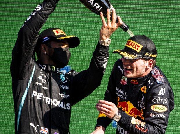Lewis Hamilton spritzt Max Verstappen bei der Siegerehrung in Zandvoort 2021 mit Champagner voll