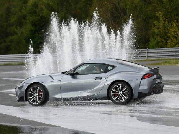 Ein grauer Toyota Supra ist seitlich zu sehen, er fährt auf durchnässter, spiegelnder Strecke auf eine breite, weiße Wasserfontäne zu.