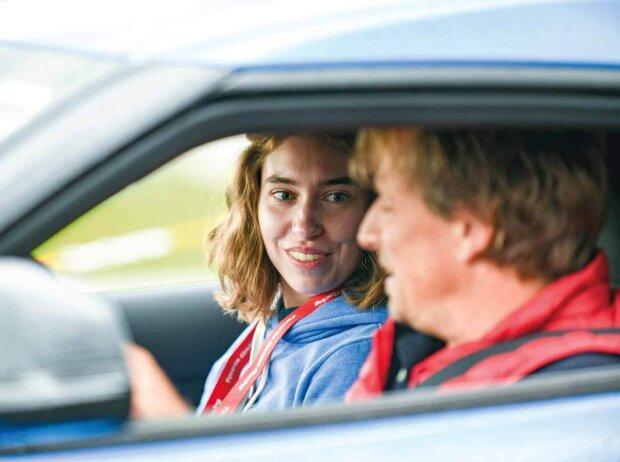 Seitlicher Blick in ein Auto. Eine Frau sitz auf dem Beifahrersitz eines Autos und schaut einen Mann an, der auf dem Fahrersitz sitzend etwas erklärt.
